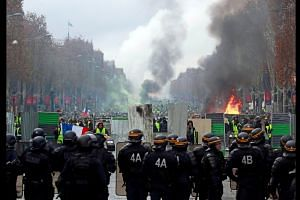 French police fire tear gas at fuel price protesters in Paris