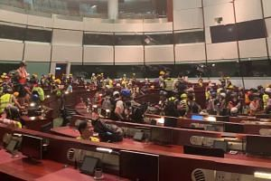 Protesters inside the Legislative Chamber after breaking into the Legislative Council building