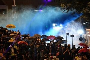 After peaceful protests, Hong Kong police fire water cannon