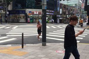 """Two """"smartphone zombies"""" spotted at a major pedestrian crossing near to Seoul City Hall"""