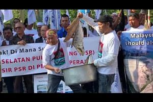 Protesters sprinkling sand on fish, a metaphor for reclamation