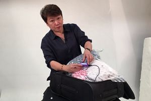 Health supplements distributor Linda Chan demonstrates how to use a Vago baggage compression device
