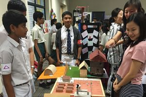 Secondary 2 students Mark Joshua John (in cardigan), Pranav Ghosh (far left) and Kenji Ng (partially hidden) showing visitors their model of the Auschwitz concentration camp at the recent National Schools Literature Festival.