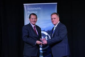 Mr Andrew Buay (at left), vice- president of group corporate social responsibility at Singtel, receiving the stakeholder engagement and materiality award from Mr Tony Gourlay, chief executive of Global Initiatives.