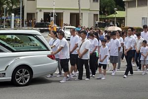 Mourners at the funeral procession for Madam Yep and her daughter, Kimberly, as their hearses leave for Mandai Crematorium yesterday.