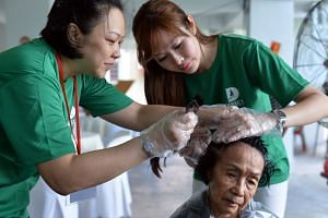 Ms Jenny Tay (right) and a volunteer dyeing the hair of Madam Florence Ho, 85, at the void deck of Block 4, Marsiling Road.