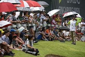 Spectators gather at the 18th hole at Sentosa Golf Club's Serapong Course at the SMBC Singapore Open yesterday. The tournament drew close to 20,000 spectators from Thursday to yesterday.