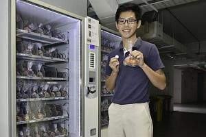 Sec 4 student Kevyn Yong Qing Yuan, 16, of the School of Science and Technology, buying fruit from the fruit dispensing machine using a token.
