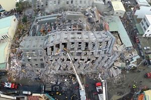 An aerial shot of Wei-guan Golden Dragon Building in Tainan city, where most of the casualties in the quake were found. Cooking oil cans reportedly found in the debris of its pillars have raised questions on its structural safety. A probe will be lau