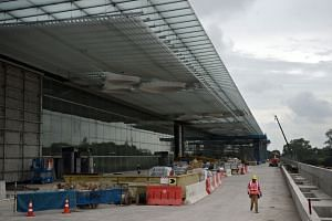 Construction of the exterior of the new Changi Airport Terminal 4 (above) is close to completion, with the focus shifting soon to the interior and ensuring T4 is ready for operations in the second half of next year. Among the works are a new bridge (