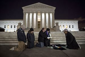People praying in front of the US Supreme Court in Washington, DC. Justice Antonin Scalia, who died in his sleep last Saturday, was a staunch defender of the values of conservative America.
