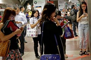 Commuters at City Hall MRT station. A mobile airwave auction will take place in the third quarter and the fourth telco could be rolling out its services as early as April next year.
