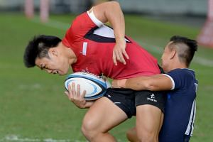 Singapore centre Nicholas Yau - who scored the home team's only try - is tackled during the 19-5 defeat by Thailand in the final of the South-east Asia Sevens at the National Stadium yesterday.