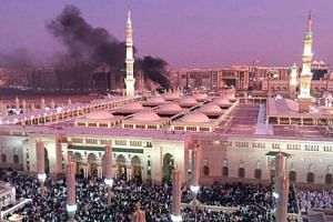 Smoke rising after a bombing near the Prophet's Mosque in Medina, Saudi Arabia, on Monday. Singapore's Ministry of Foreign Affairs has condemned strongly the attacks in three places in Saudi Arabia.