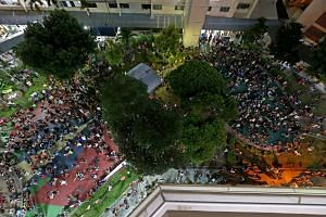 Pokemon Go players crowding in front of Block 401, Hougang Avenue 10, last Saturday. Large numbers have gathered daily at the hot spot, mainly at the amphitheatre and playground between Blocks 401 and 415, a strategic place for catching the game's vi