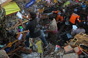 Rescuers looking for survivors in Pidie Jaya, Aceh province, yesterday. Many are still trapped under the rubble of collapsed buildings. Hundreds of residents and volunteers have joined rescue efforts.