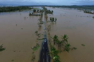 A flooded highway after Nock-Ten made landfall in Albay province in the Philippines yesterday. More than 383,000 people spent Christmas in shelters, while over 80 flights were cancelled, the civil defence office said.