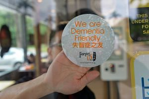 A decal being placed on the window of a McDonald's outlet in Yishun, indicating that restaurant staff are trained to help those with dementia. Yishun is one of three estates where some residents and businesses are trained to spot and help people with