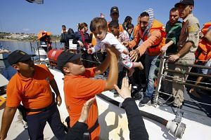 Members of the Turkish coast guards holding a baby of a Syrian migrant on the shore in Cesme, near the Aegean port city of Izmir, Turkey, on Aug 11, 2015.