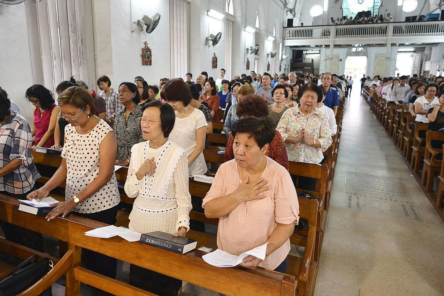 About 500 Singaporeans and Filipinos attended a solidarity mass led by Archbishop William Goh at the Church of Saints Peter and Paul on Tuesday evening. -- ST PHOTO: ASHLEIGH SIM