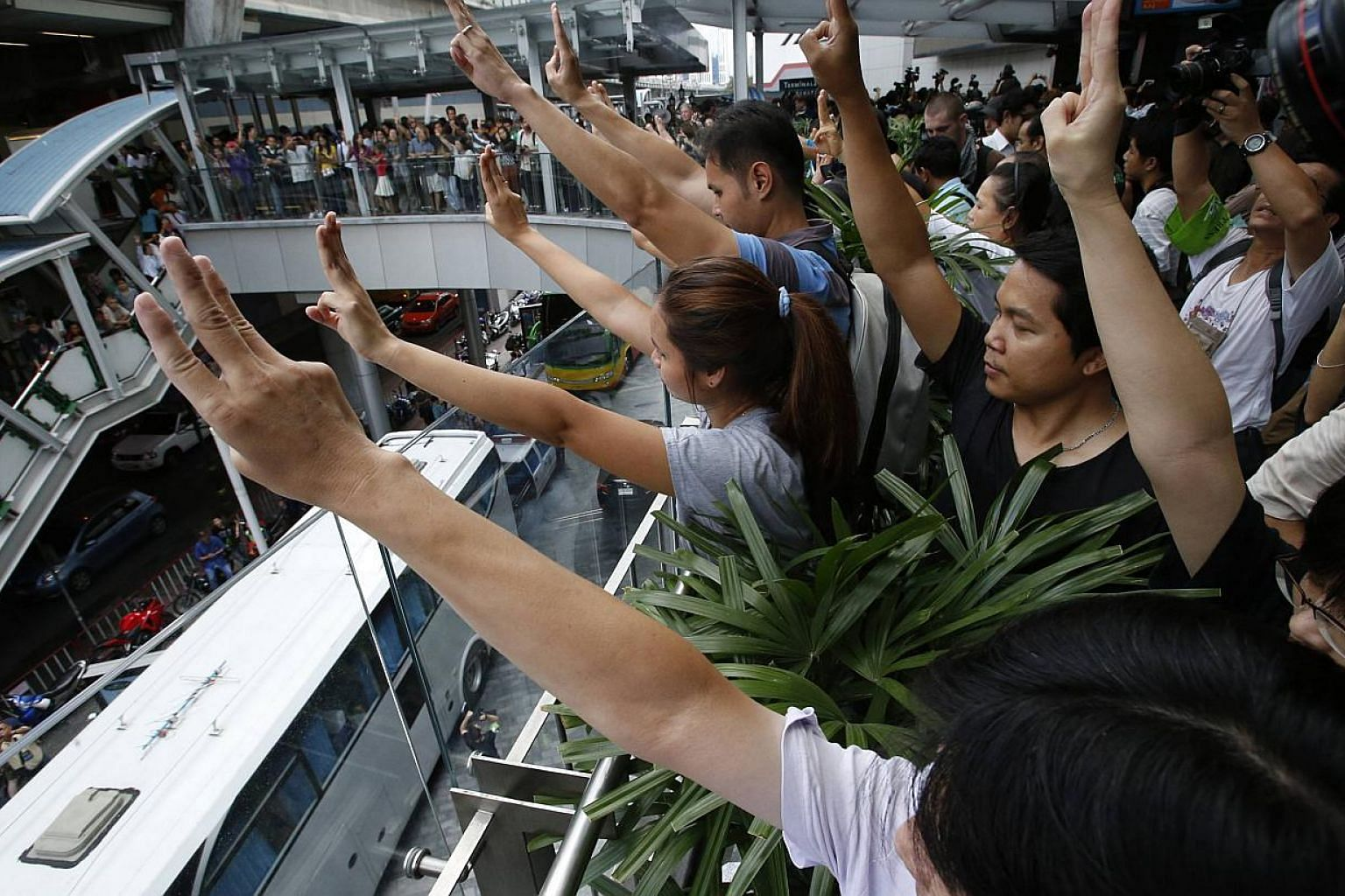 Protesters against military rule gesture by holding up their three middle fingers in the air, during a brief demonstration at a shopping mall in Bangkok on June 1, 2014. Supporters of Thailand's military junta are trying to hijack a gesture used by d