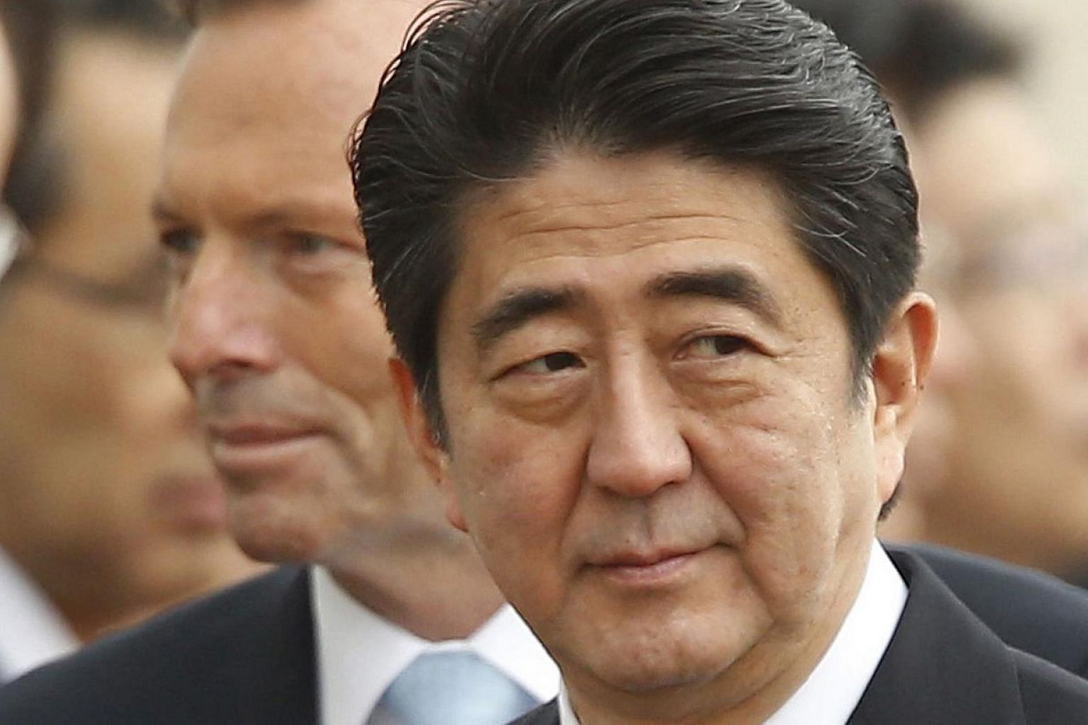 Japan's Prime Minister Shinzo Abe (right) participates in an official arrival ceremony with Australian Prime Minister Tony Abbott (back left) at Parliament House in Canberra on July 8, 2014.Japanese Prime Minister Shinzo Abe has been personally