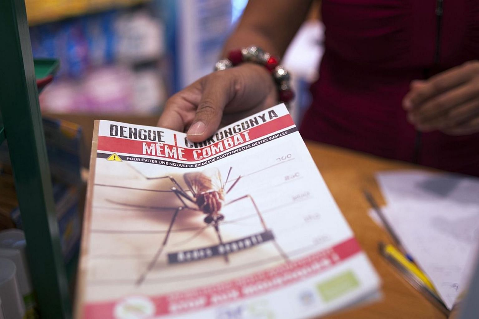A picture taken on July 10, 2014, shows a shopkeeper handing to a customer some documentation about the mosquito-born chikungunya virus at a drugstore in Lamentin, near Fort-de-France, on the French Caribbean island of La Martinique. -- PHOTO: A