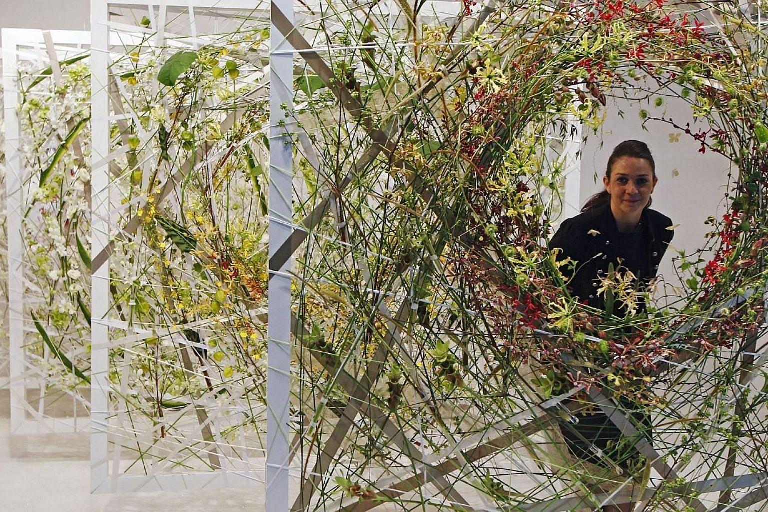 Annette von Einem of Denmark poses for photos in her floral display creation, The Ice Queen Spring Breath, during the Singapore Garden Festival 2014. -- PHOTO: REUTERS