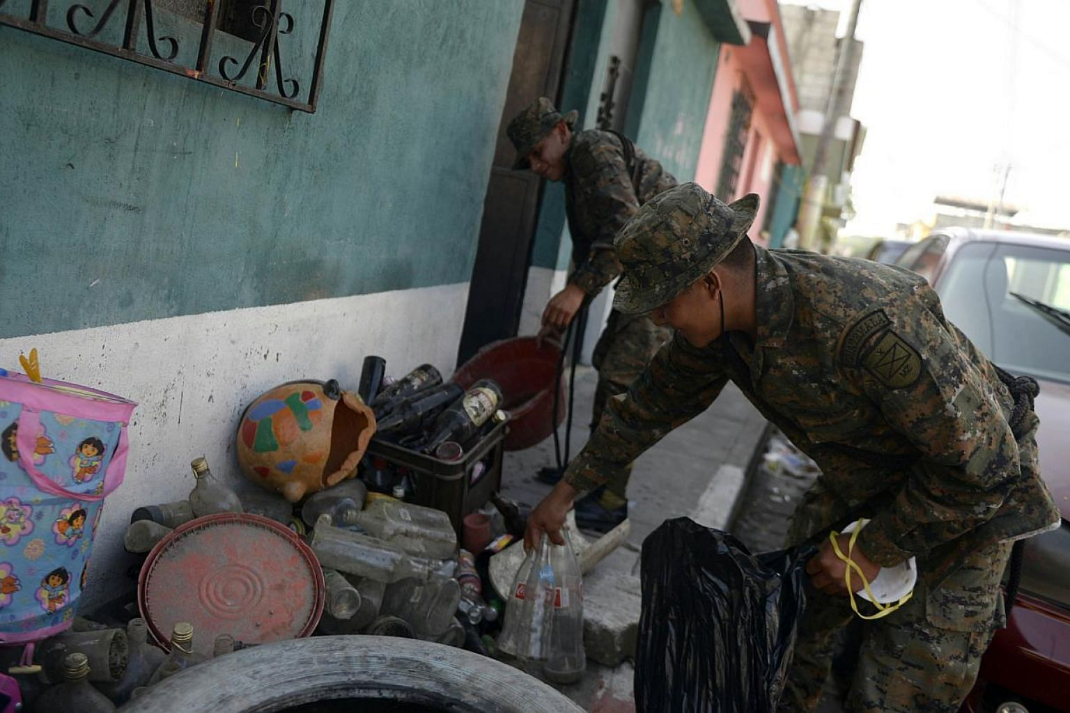 Soldiers take part in a campaign to eliminate potential breeding sites of the Aedes mosquito which transmits dengue and chikungunya, in Amatitlan, 33km south of Guatemala City, on Nov 24, 2014. -- PHOTO: AFP