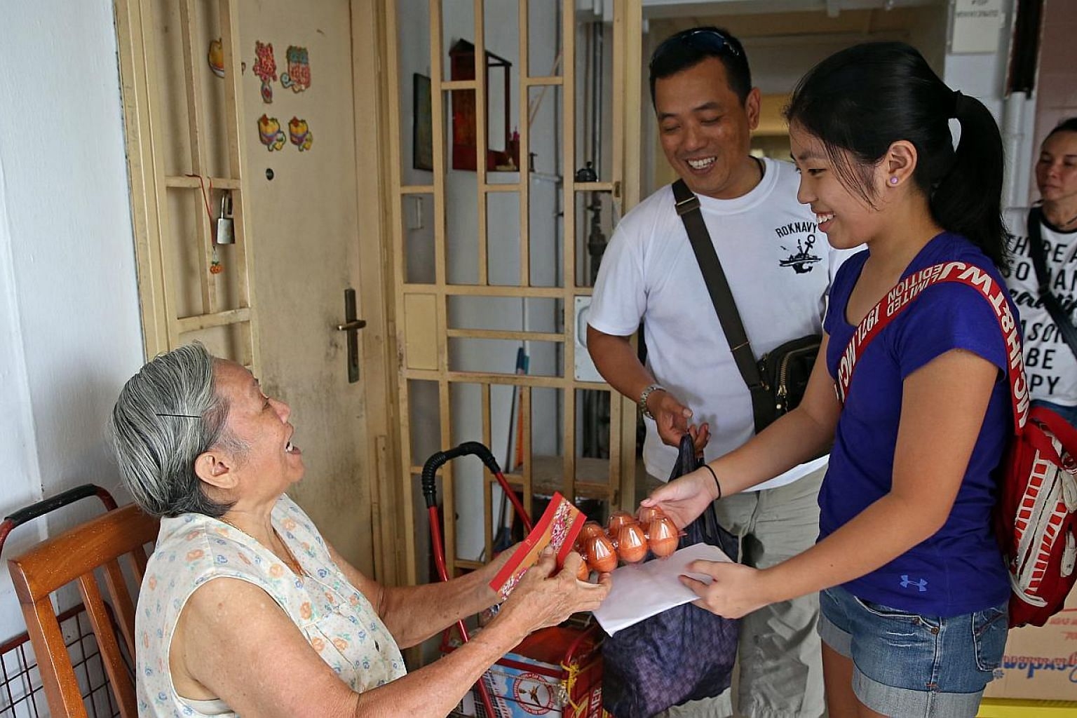 Mr Mervyn Chua, 48, and his daughter Ryen, 12, distributing food to Madam Liow Mee Yin, 75, as well as other elderly folk living alone in Jalan Kukoh. The Chuas are members of Friends in Charity, an informal group of volunteers who give food and cash