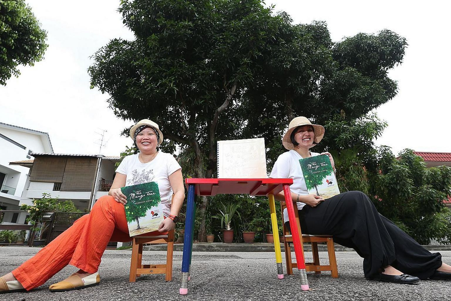 "Local writers Lee Seow Ser (left) and Hidayah Amin, with the Braille and non-Braille versions of Ms Hidayah's The Mango Tree. The Braille version of the 32-page book for children has 10 pages, of which only one has illustrations. ""If we had more mone"