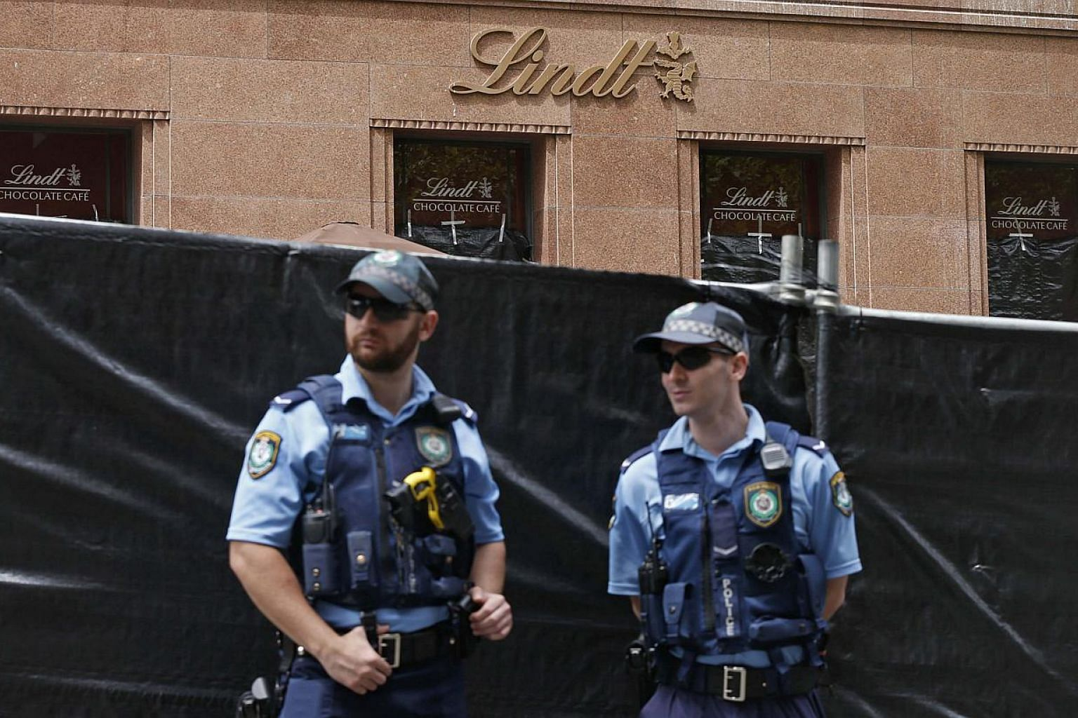 New South Wales police officers guard a post near the fenced-off site of the siege at the Lindt cafe in Martin Place, Sydney, Australia on Dec 17, 2014. -- PHOTO: REUTERS