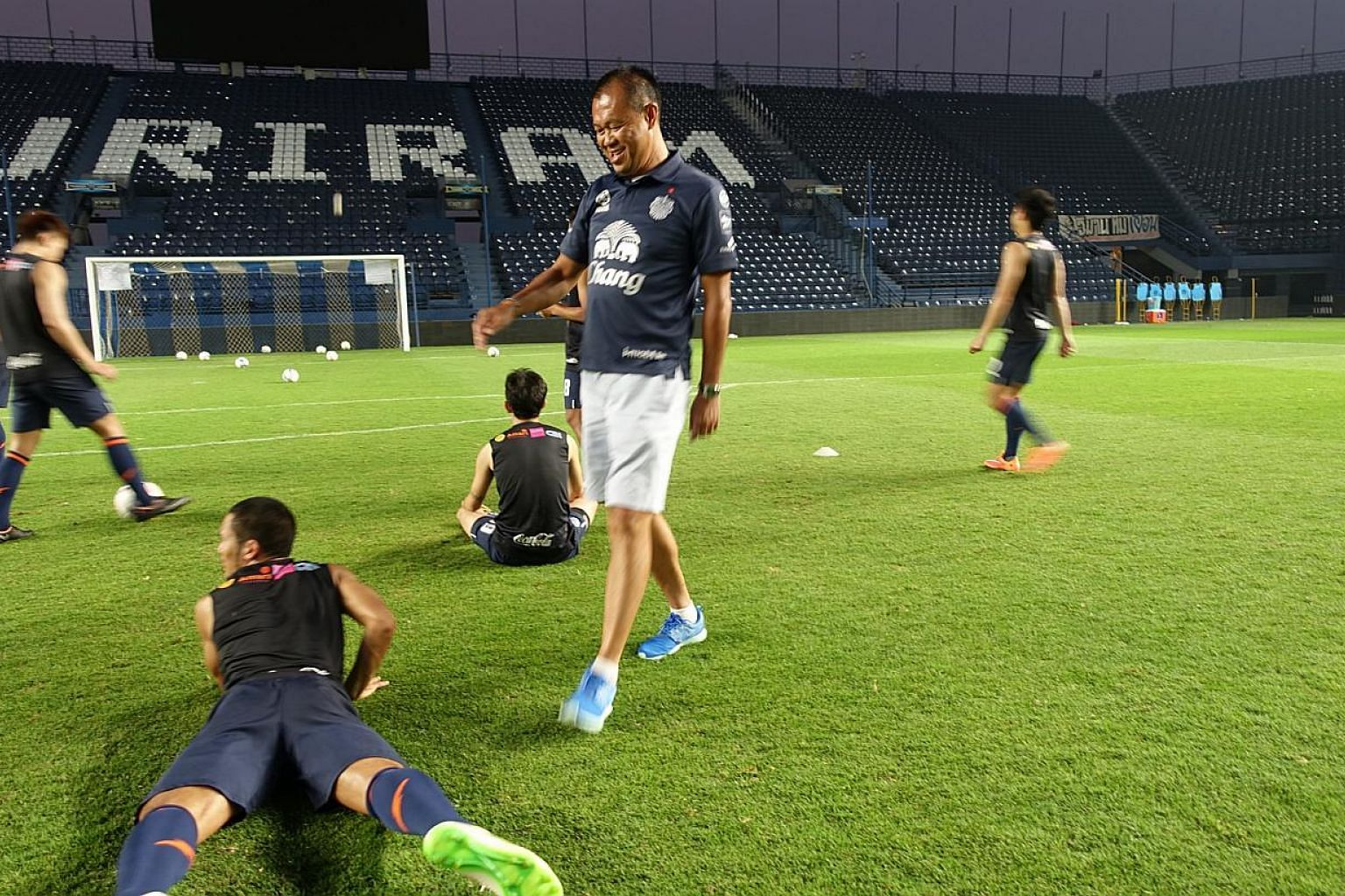 Newin Chidchob (in blue shoes) with Buriram United footballers during training. -- ST PHOTO: TAN HUI YEE