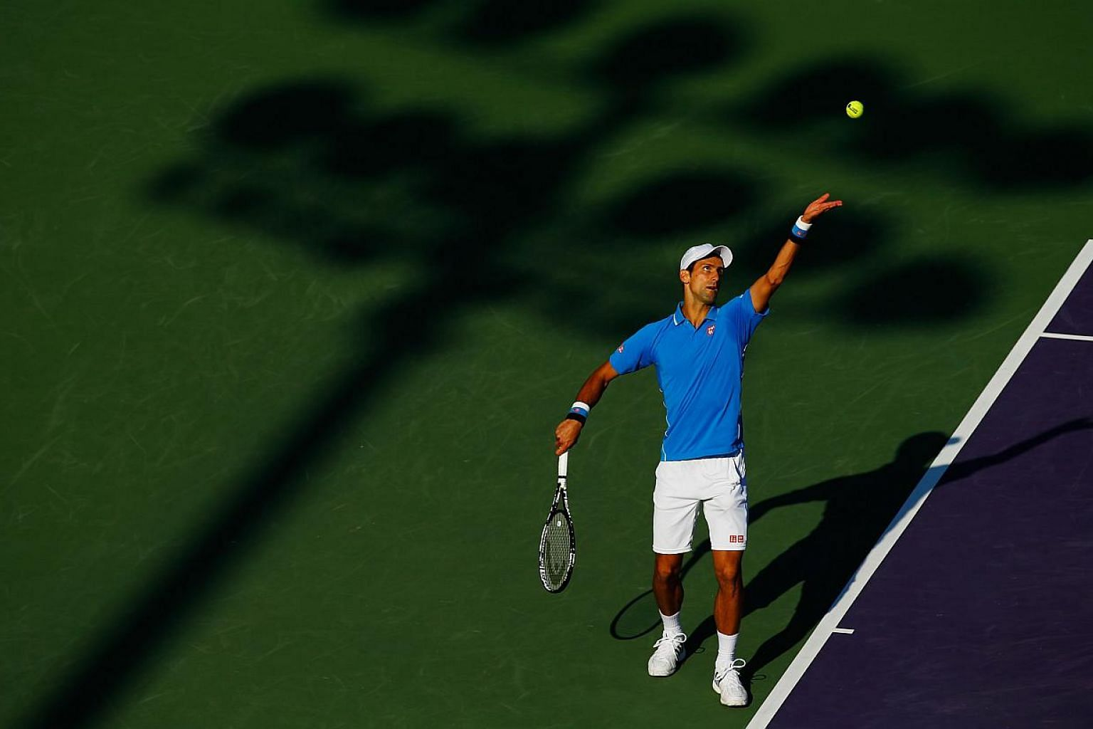 Novak Djokovic serving against Alexandr Dolgopolov during day 9 of the Miami Open at Crandon Park Tennis Center on March 31, 2015, in Key Biscayne, Florida. -- PHOTO: AFP