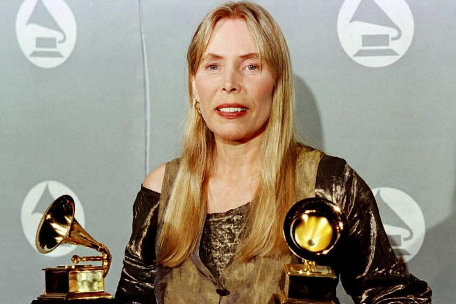 "This February 28, 1996 file photo shows singer Joni Mitchell holding two Grammy Awards for Best Pop Album, ""Turbulent Indigo,"" during the 38th Annual Grammy Awards in Los Angeles. -- PHOTO: AF"