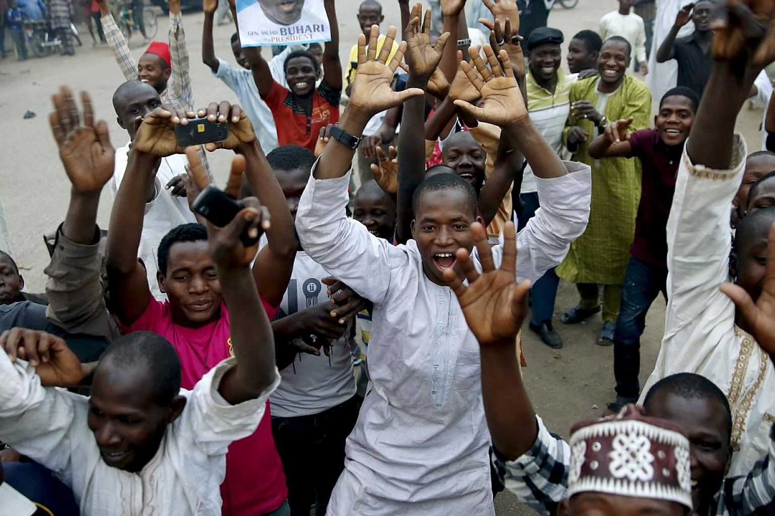 Supporters of the presidential candidate Muhammadu Buhari and his All Progressive Congress (APC) party celebrate in Kano on Tuesday. Three after Buhari became the first Nigerian to oust a president through the ballot box, putting him in charge of Afr