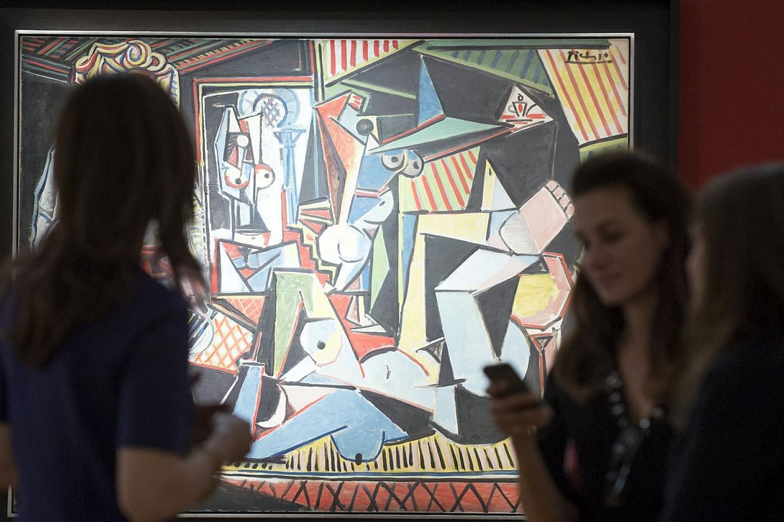 "People look at Pablo Picasso's ""Les femmes d'Alger (Version 'O')"" (Women of Algiers), estimated at US$140 million, ahead of a preview event to Christie's upcoming impressionist, modern and contemporary art sale in Manhattan on May 1, 2015. -- PHOTO:"