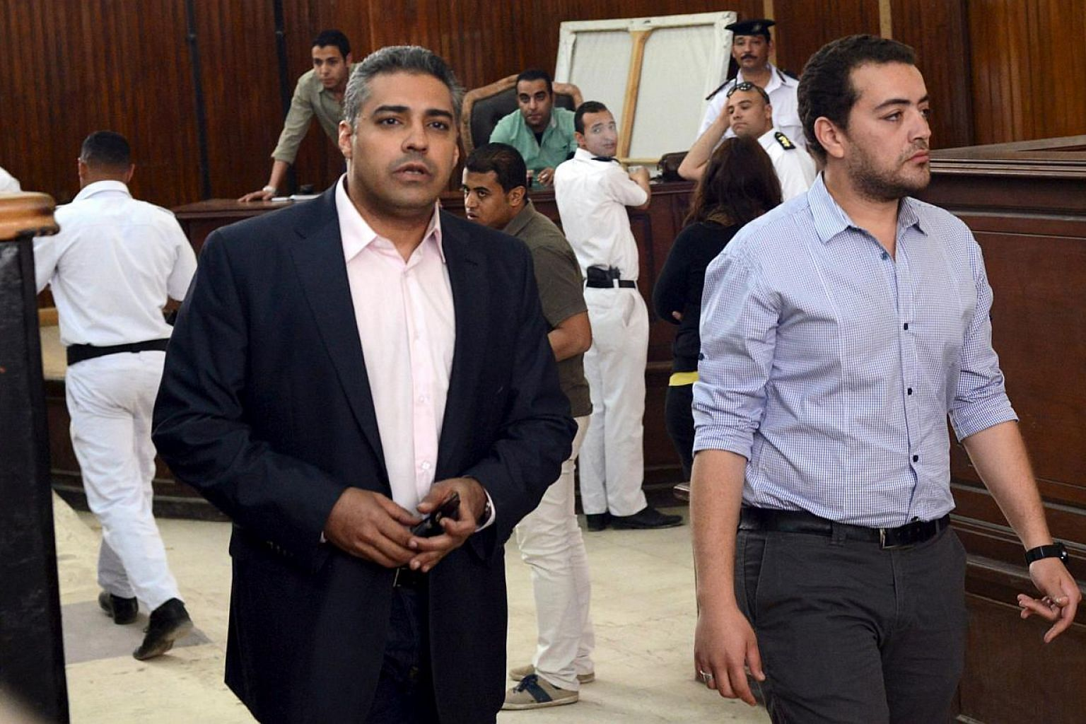 Al-Jazeera television journalists Mohamed Fahmy (left) and Baher Mohamed are seen at a court in Cairo on April 22, 2015. They are undergoing a retrial after a court found procedural flaws in the original case. -- PHOTO: REUTERS