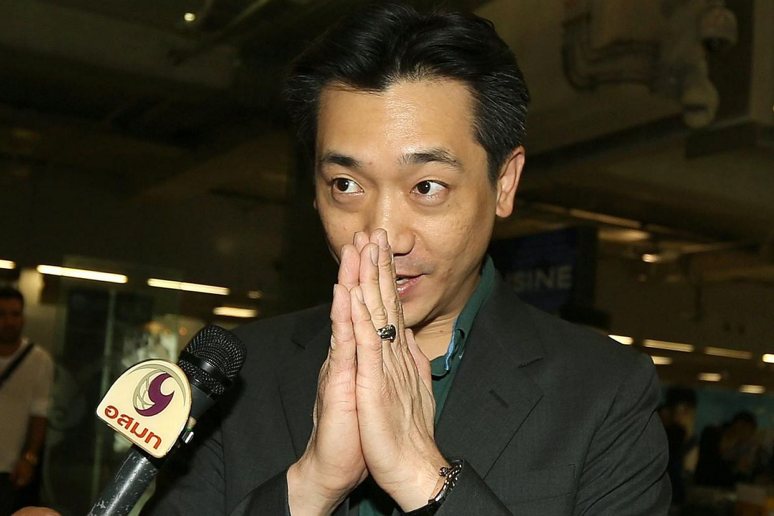Thai businessman Bee Taechaubol greets the press as he arrives to the Suvarnabhumi airport, after returning from Milan. -- PHOTO: EPA