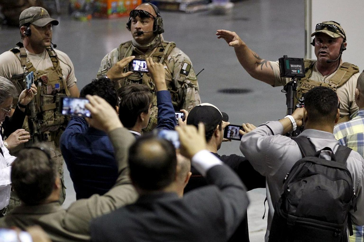 Police officers address attendees at the Muhammad Art Exhibit and Contest. Two gunmen opened fire at an anti-Islam art show featuring depictions of the Prophet Mohammad in Garland, Texas, near Dallas on Sunday. -- PHOTO: REUTERS