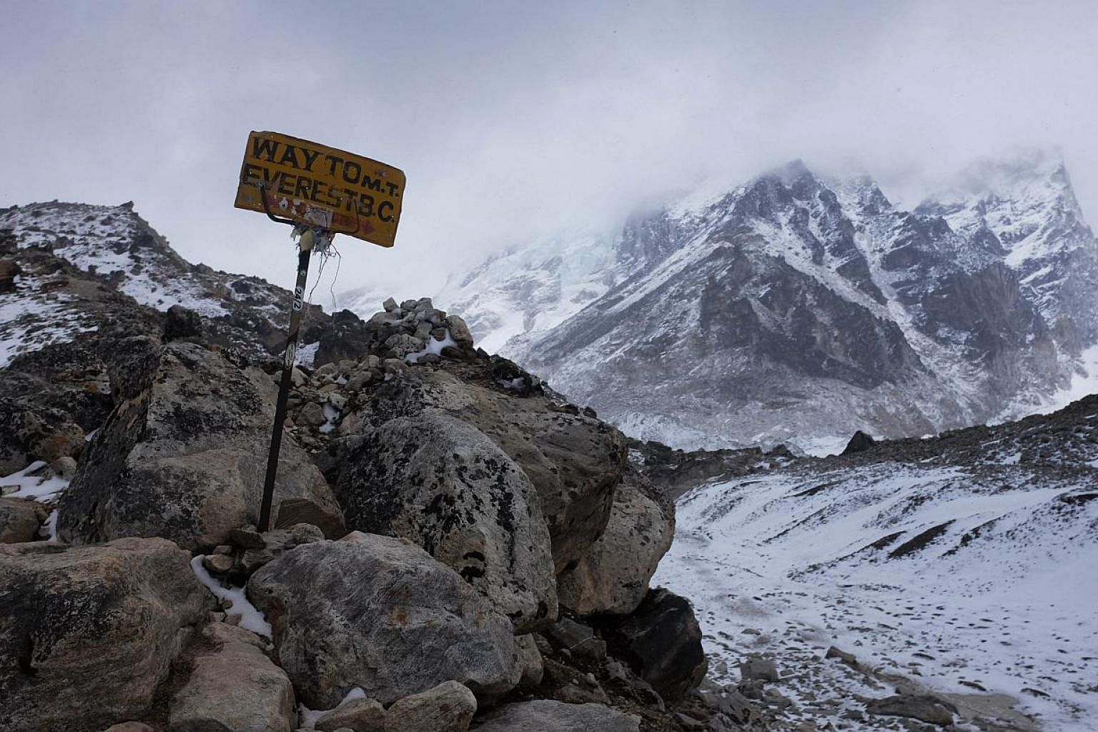 A sign showing the way to Everest Base Camp high in the Khumb Glacier stands among rocks on April 26, 2015, one day after an earthquake triggered avalanche swept through parts of the base camp killing scores of people. -- PHOTO: AFP