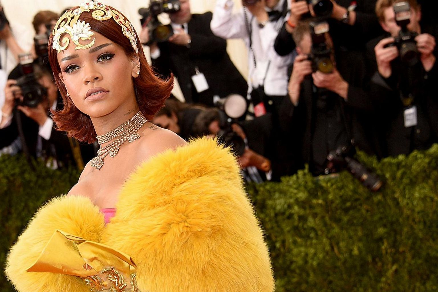 Rihanna wearing a gold tiara and flowing yellow robe at the New York Met Ball on May 4, 2015. The city's party of the year, attended by stars such as Madonna, George Clooney, Sarah Jessica Parker and Robert Pattinson, chose China as the theme of its