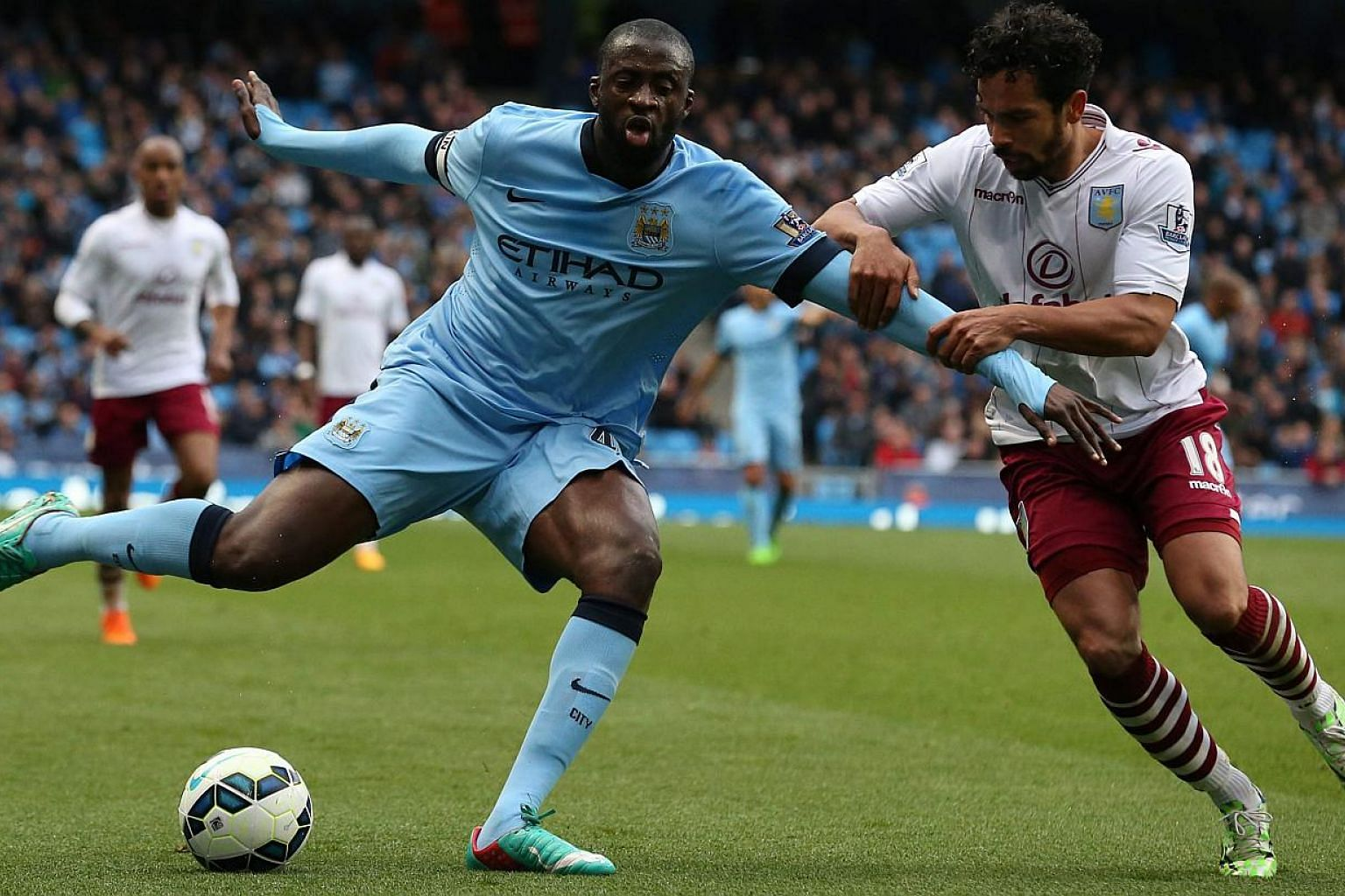 Aston Villa's Kieran Richardson (right) challenges Manchester City's Yaya Toure during the English Premier League soccer match between Manchester City and Aston Villa at the Etihad stadium in Manchester, Britain, April 25, 2015. -- PHOTO: EPA