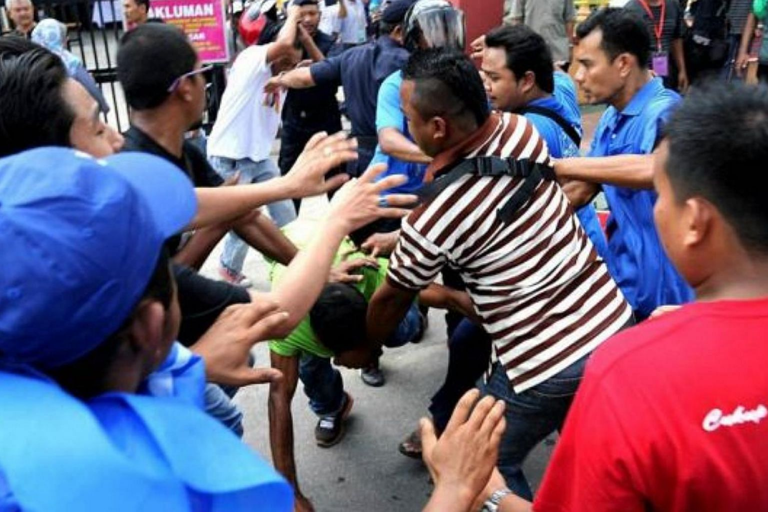 Rival supporters clash outside SK Tanah Liat polling centre during the Permatang Pauh by-election. -- PHOTO: THE STAR/ASIA NEWS NETWORK