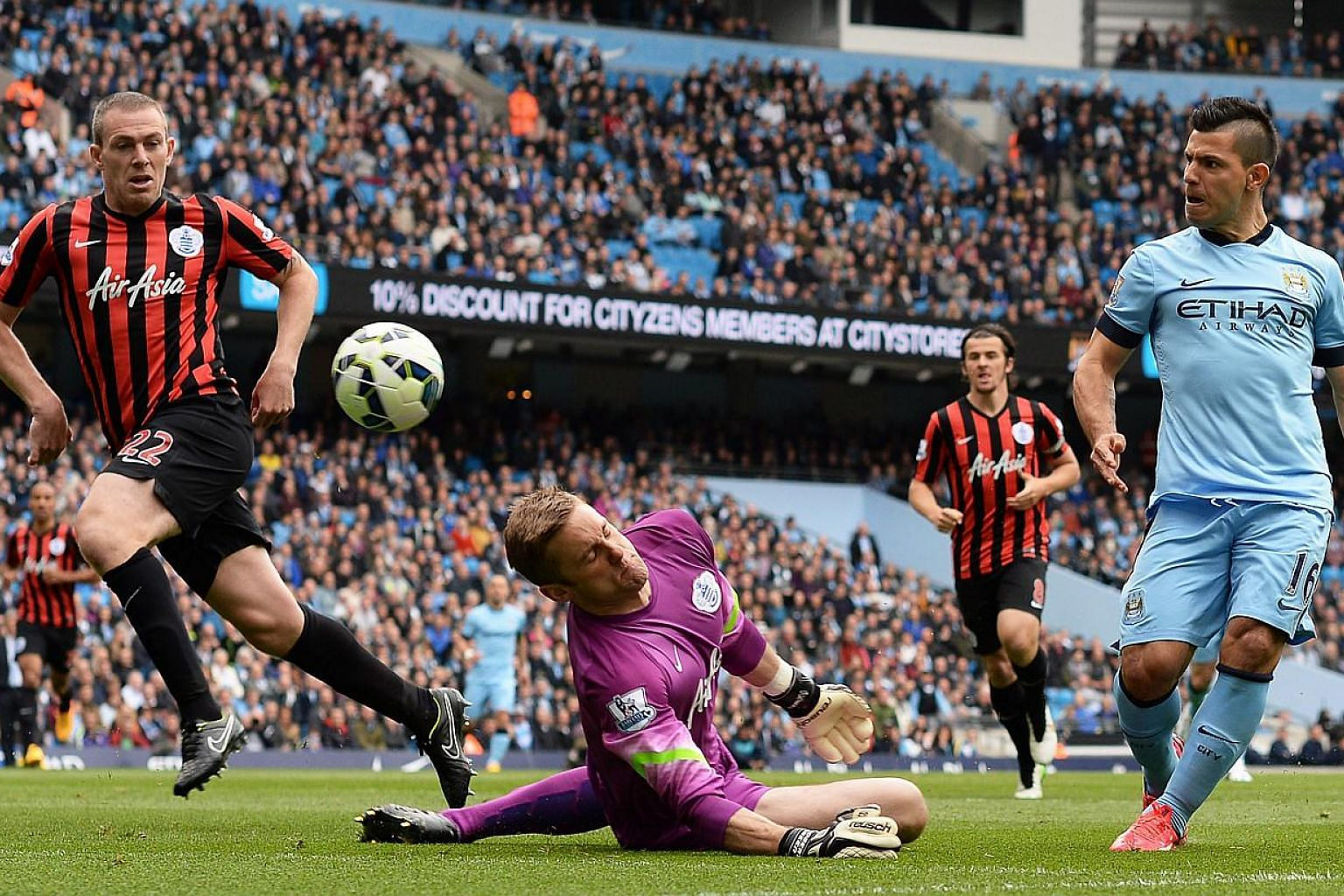 Manchester City's Sergio Aguero (right) scores the 1-0 lead against Queens Park Rangers' goalkeeper Robert Green (centre) during the English Premier Leaguefootball match in Manchester, Britain on May 10, 2015. -- PHOTO: EPA