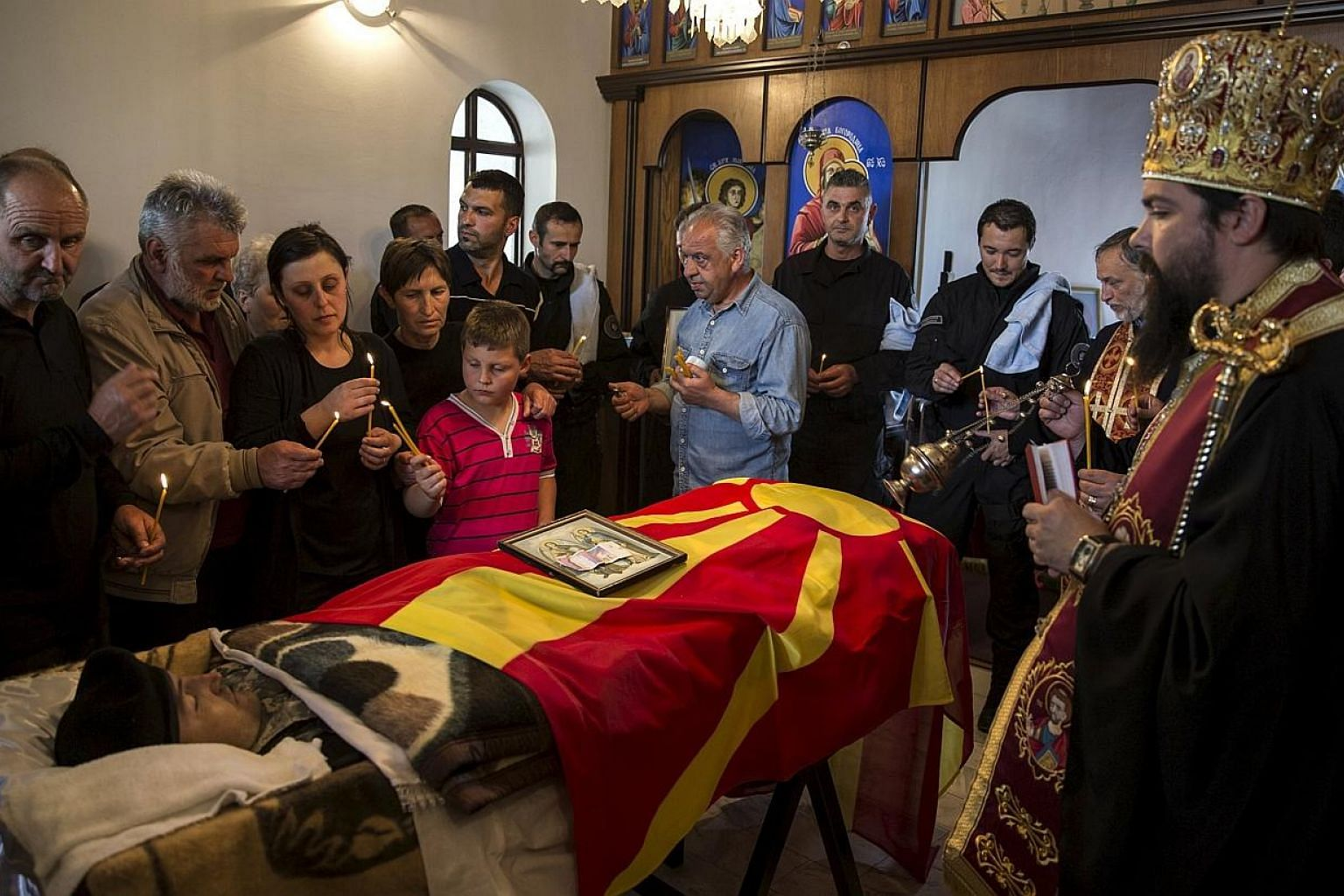 Relatives of policeman Zarko Kuzmanovski mourn next to his coffin draped with the Macedonian flag inside a church during his funeral in the village of Brvenica, Macedonia on Sunday. -- PHOTO: REUTERS