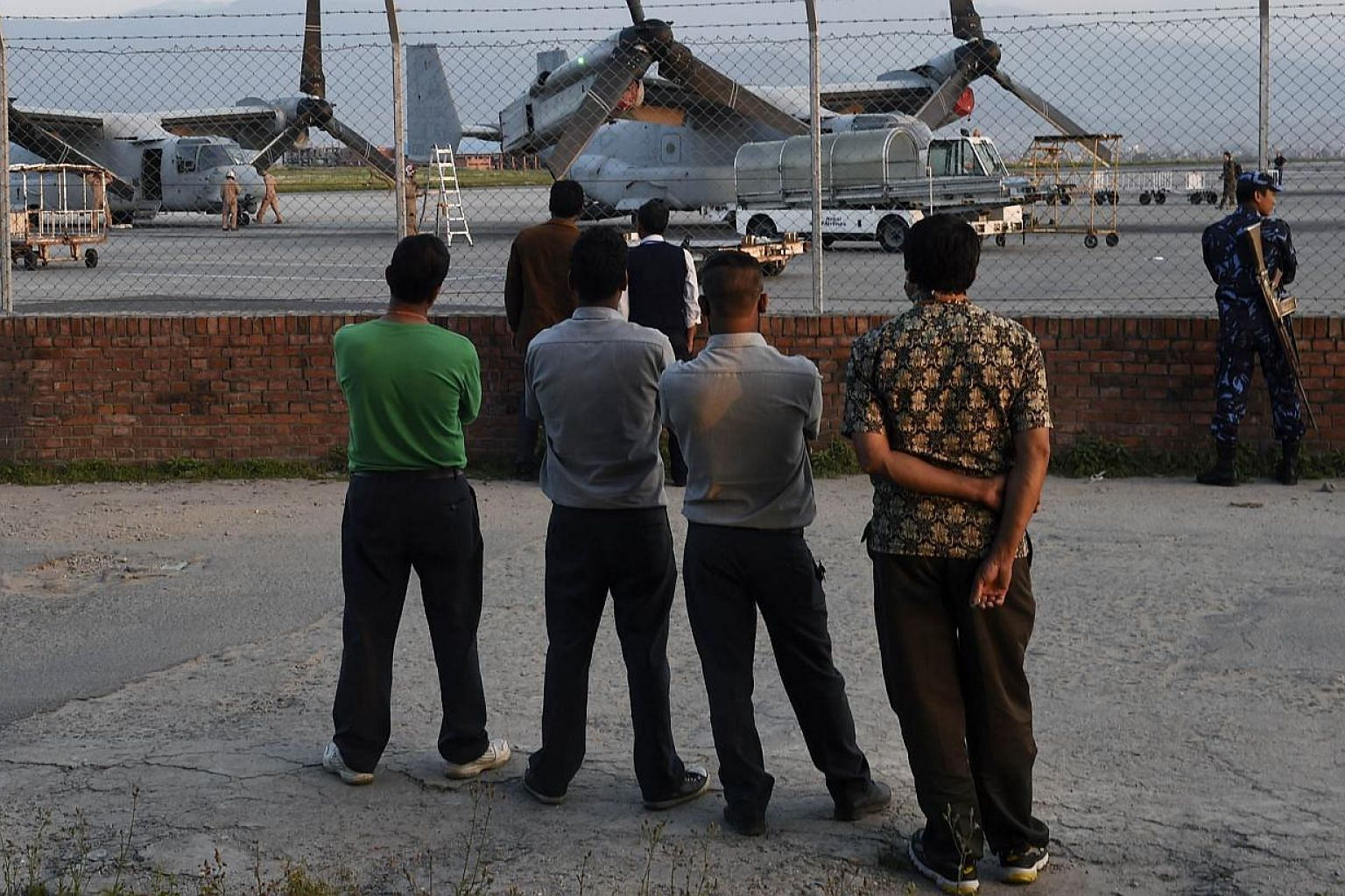 Nepalese men watching US military Osprey aircraft after they landed at Kathmandu's international airport on May 3, 2015. Nepalese authorities ordered the closure of Kathmandu airport on Tuesday after a new earthquake killed at least four people and s