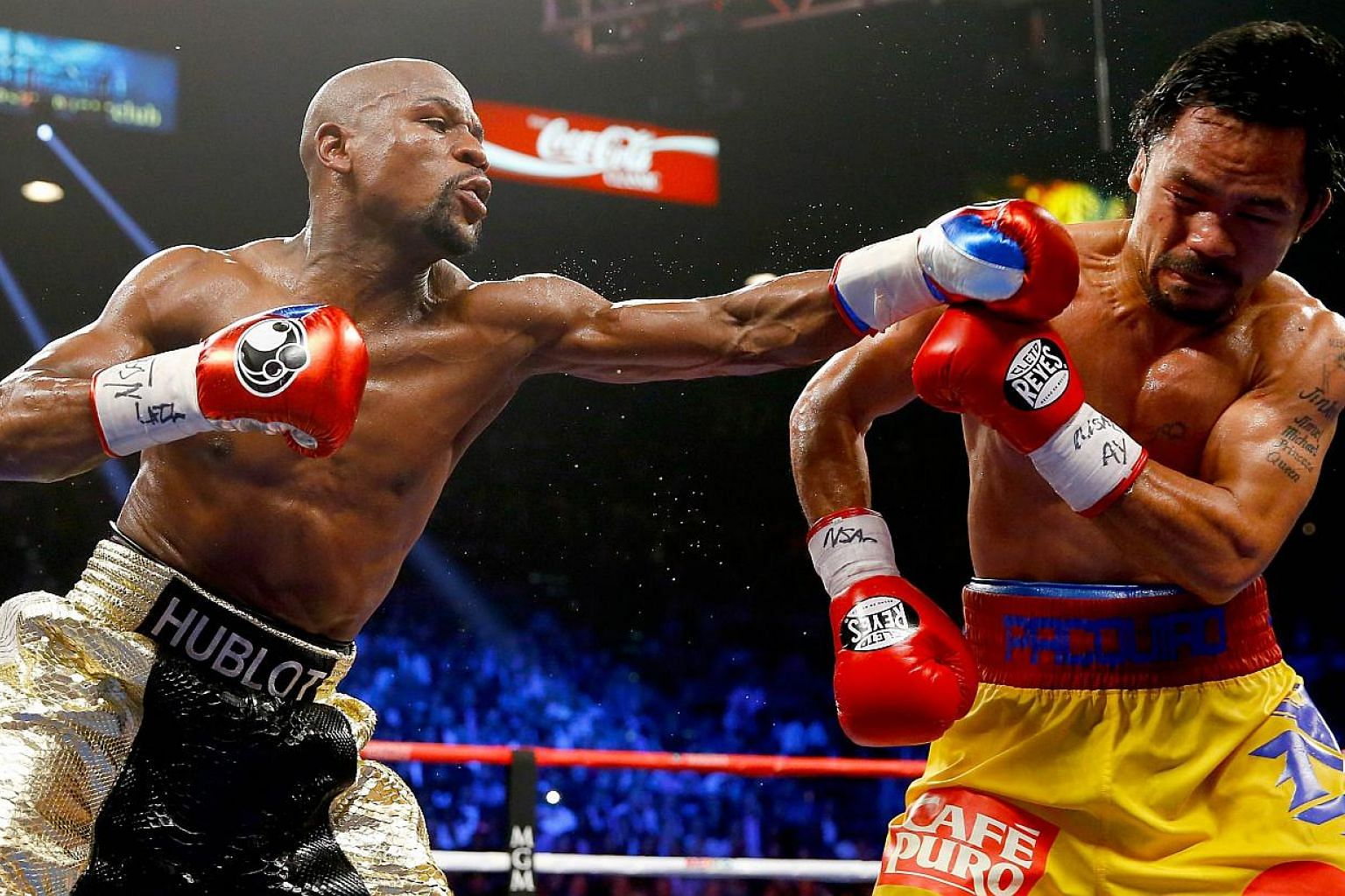 """Floyd Mayweather Jr throws a left at Manny Pacquiao during their welterweight bout on May 2, 2015 in Las Vegas, Nevada. The """"Fight of the Century"""" between boxing greats Floyd Mayweather Jr and Manny Pacquiao generated record pay-per-view re"""