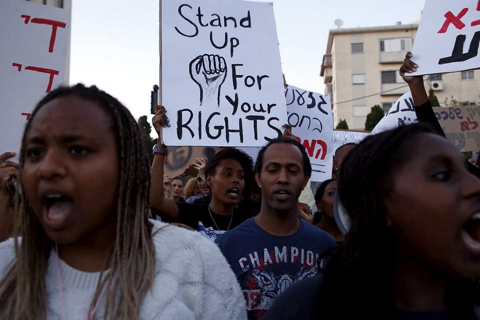 Israelis of Ethiopian descent hold signs during a protest against police brutality and racism in the northern city of Haifa, Israel May 12, 2015. -- PHOTO: REUTERS