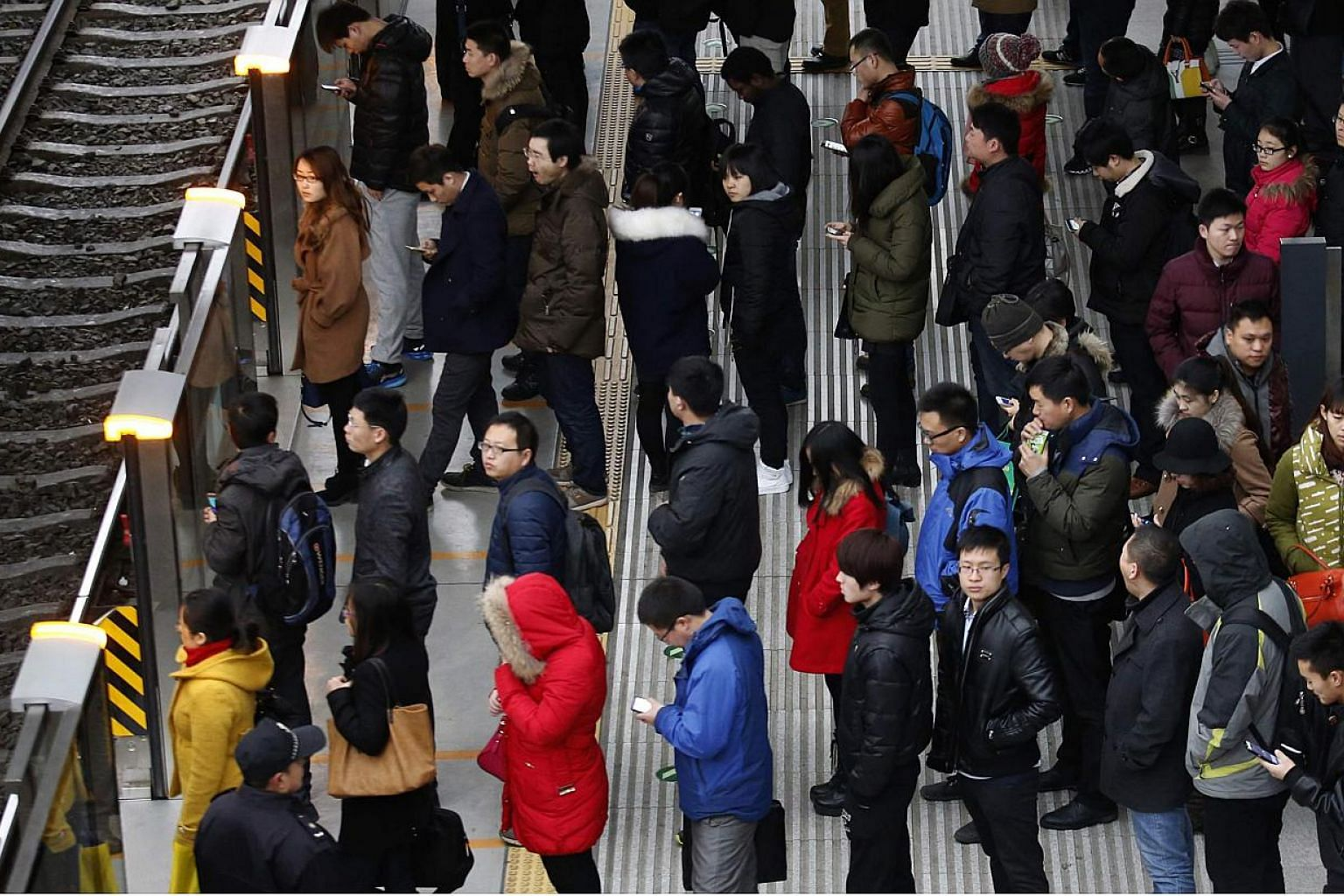 Passengers waiting for a train in Beijing on Feb 25, 2015. Beijing police are patrolling the city's subways and trains to stop people wearing face masks, strange costumes and forming flash mobs, warning commuters that such actions could jeopardise pu
